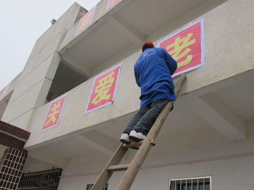 """Die Aufschrift heißt: """"Um Alte kümmern"""" und wird zur Einweihung an dem ehem. Schulgebäude angebracht"""