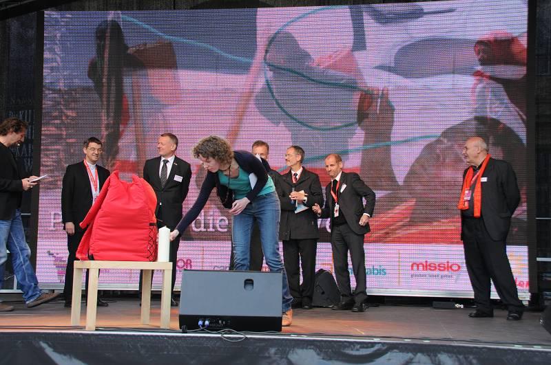 Auf der Bühne des Toulonplatzes packen die Geschäftsführer der katholischen Werke ihren Rucksack für einen neuen Aufbruch.