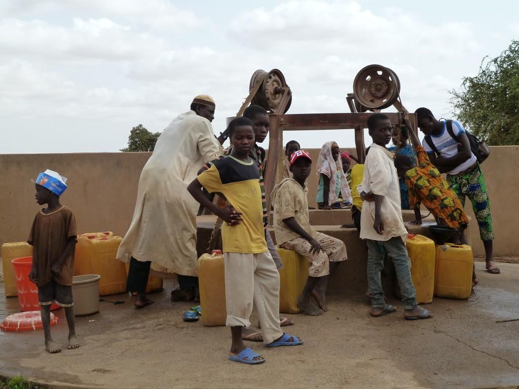 Kinder holen Wasser am Brunnen