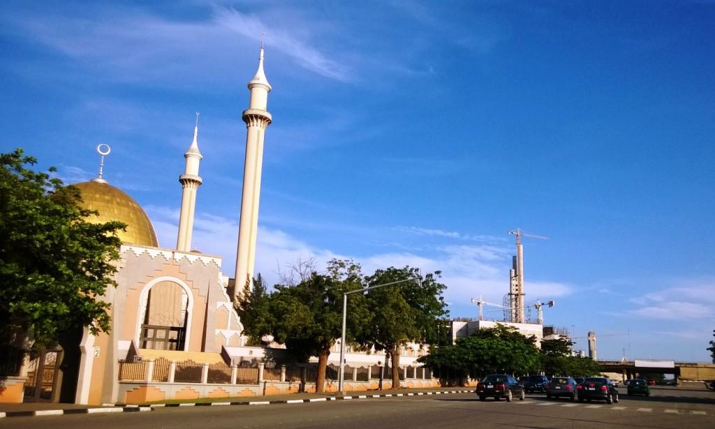 """Die Nationalmoschee zählt ebenso wie die Nationalkirche (rechts im Hintergrund) zu den Wahrzeichen Abujas. Dazwischen befindet sich das """"Unity Centre"""" im Bau, das als Symbol der Einheit Nigerias dienen soll."""