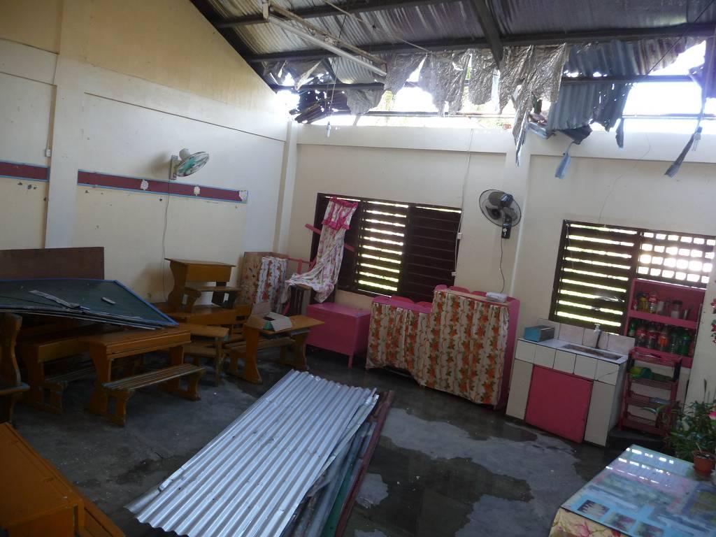 Mrs. Biba zeigt uns ihre Schulklasse, bei der das Dach teilweise vom Sturm weggefegt wurde.