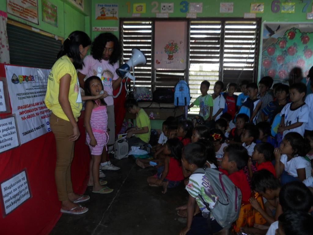 das Mädchen erzählt den anderen Kindern, wie es den Taifun erlebt hat.