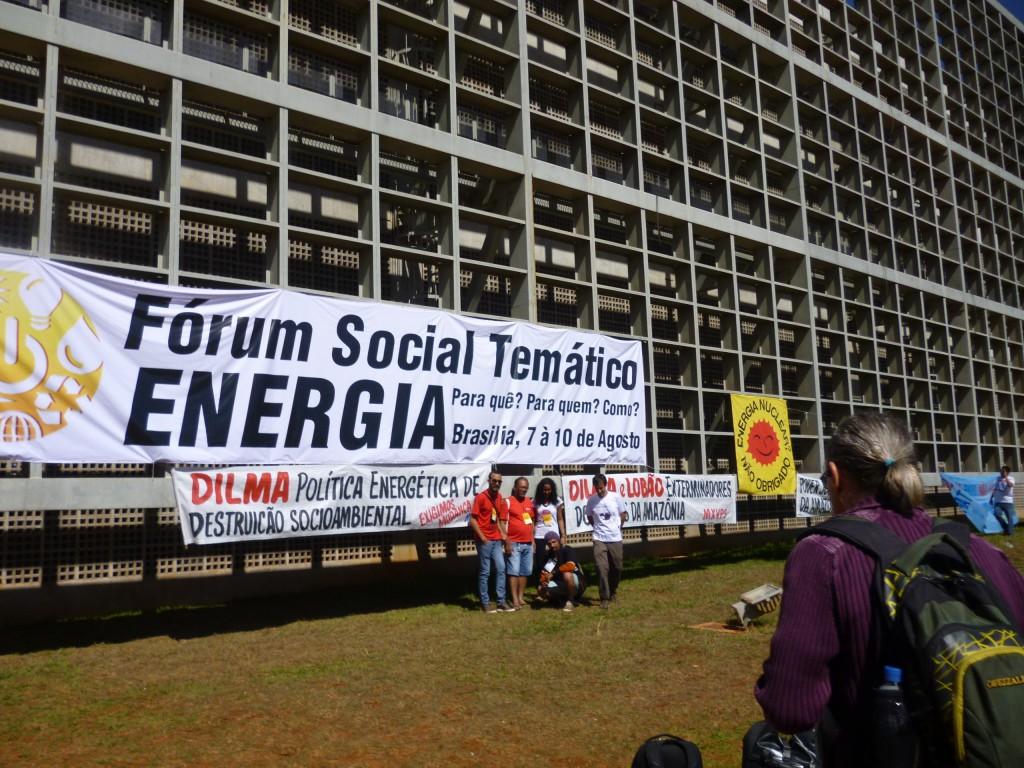 """Vor der Universität Brasílias: unter dem offiziellen Banner des Sozialforums haben Bewegungen und Arbeitsgruppen ihre Kritik und Forderungen angebracht: """"Dilma. Energiepolitik der Umweltzerstörung. Wir fordern einen Wandel."""" Weiter im Hintergrund """"Atomkraft. Nein danke."""""""