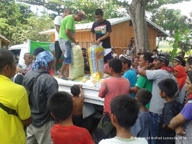 Verteilung von Lebensmitteln in einem provisorisch eingerichteten Lager für intern Vertriebene im Gebiet von Rajah Buayan