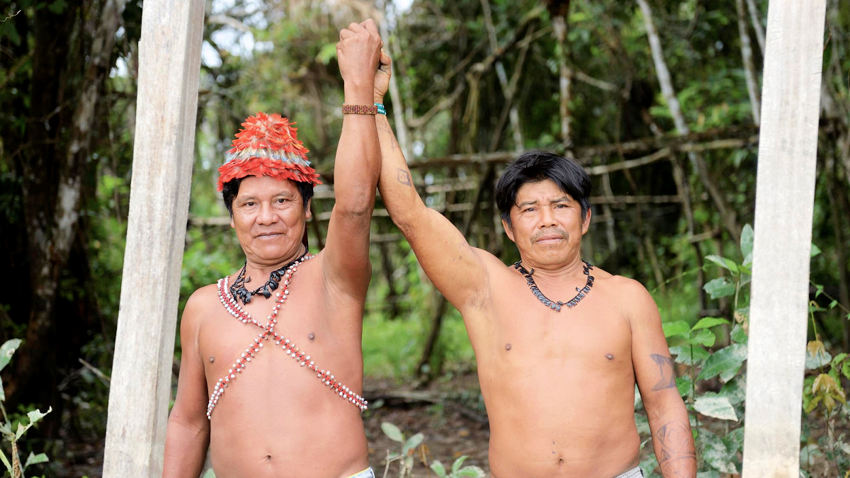 """Die Cazique der Mundurukú-Indianer Juarez und Walter an einem Schild, das die Grenze des Gebietes seines Volkes markiert. Dorf der Mundurukú Sawre Jaybu oder """"Dorf Juarez"""" (benannt nach dem Cazique Juarez) am Rio Tapajos, Distrikt Itaituba, Bundesstaat Pará, Brasilien; Foto: Florian Kopp / Misereor"""