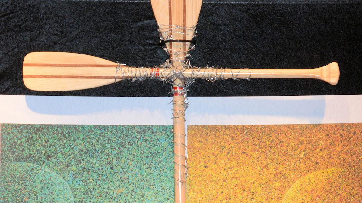 Ein Kreuz aus Paddeln vor dem MISEREOR-Hungertuch.