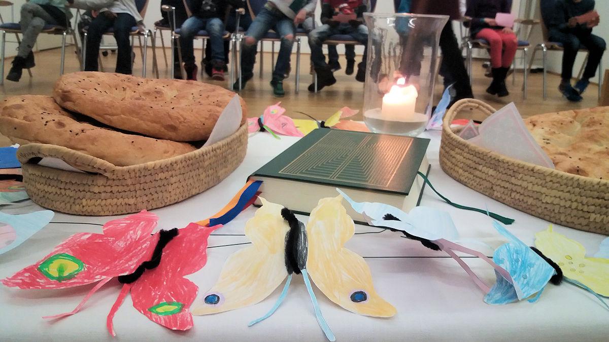 Selbstgebastelte Schmetterlinge der Schülerinnen und Schüler der Annaschule Aachen liegen in der Kreismitte beim Gottesdienst.