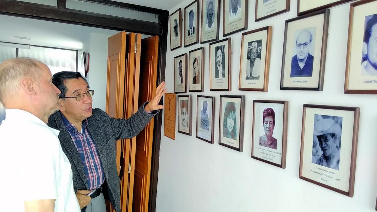 """Jaime Diaz vom MISEREOR-Partner """"Corporacion Podion"""" zeigt Pirmin Spiegel die Fotos von Menschen, die ermordet wurden wegen ihres Engagement für eine friedlichere Welt."""