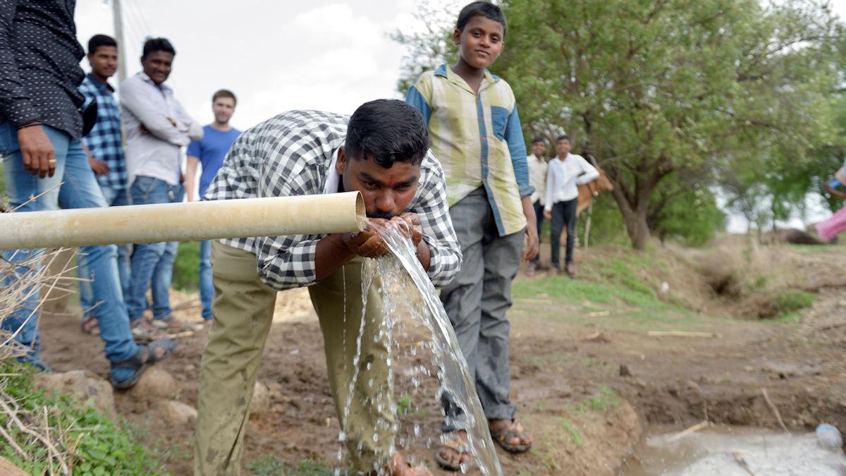 Ein Dorfbewohner trinkt das aus einem Rohr sprudelnde Wasser. Um gegen die wiederkehrende Dürre anzugehen, haben die Dorfbewohner aus eigener Kraft - unterstützt von Caritas Indien im Rahmen des Projekts JEEVAN - 37 Kanäle und Becken ausgehoben. So wird Regenwasser gespeichert und der Grundwasserspiegel wieder angehoben, © Kopp/MISEREOR.