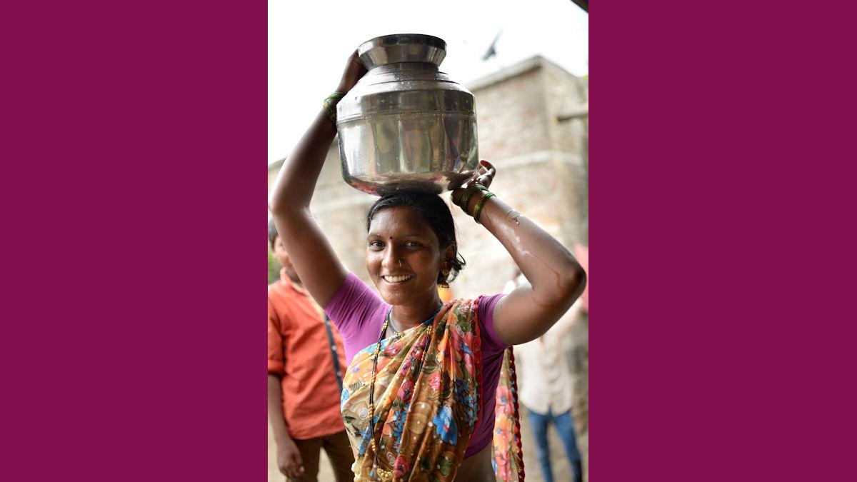 Rajeshvari Nitin Kajabe kommt mit einem Krug Wasser vom Brunnen zurück © Kopp/MISEREOR