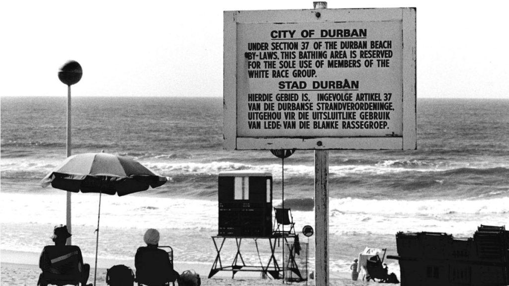 """Durban, Südafrika (1982): Ziel und Folge der Apartheid war der gesetzlich gestützte Ausschluss der nicht-weißen Bevölkerungsmehrheit von Lebensraum, politischer Mitbestimmung und Bildung. Dem Schild zu Folge ist dieser Strandabschnitt der damaligen Gesetzeslage entsprechend """"für die alleinige Nutzung von Mitgliedern der weißen Rasse reserviert"""". © KNA-Bild/MISEREOR"""