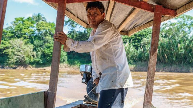 Santos Cáceres am Steuer seines Motorboots auf dem Río Madre de Dios. Der Holzbaldachin bietet Schutz vor der Sonne. © Eduardo Soteras / MISEREOR
