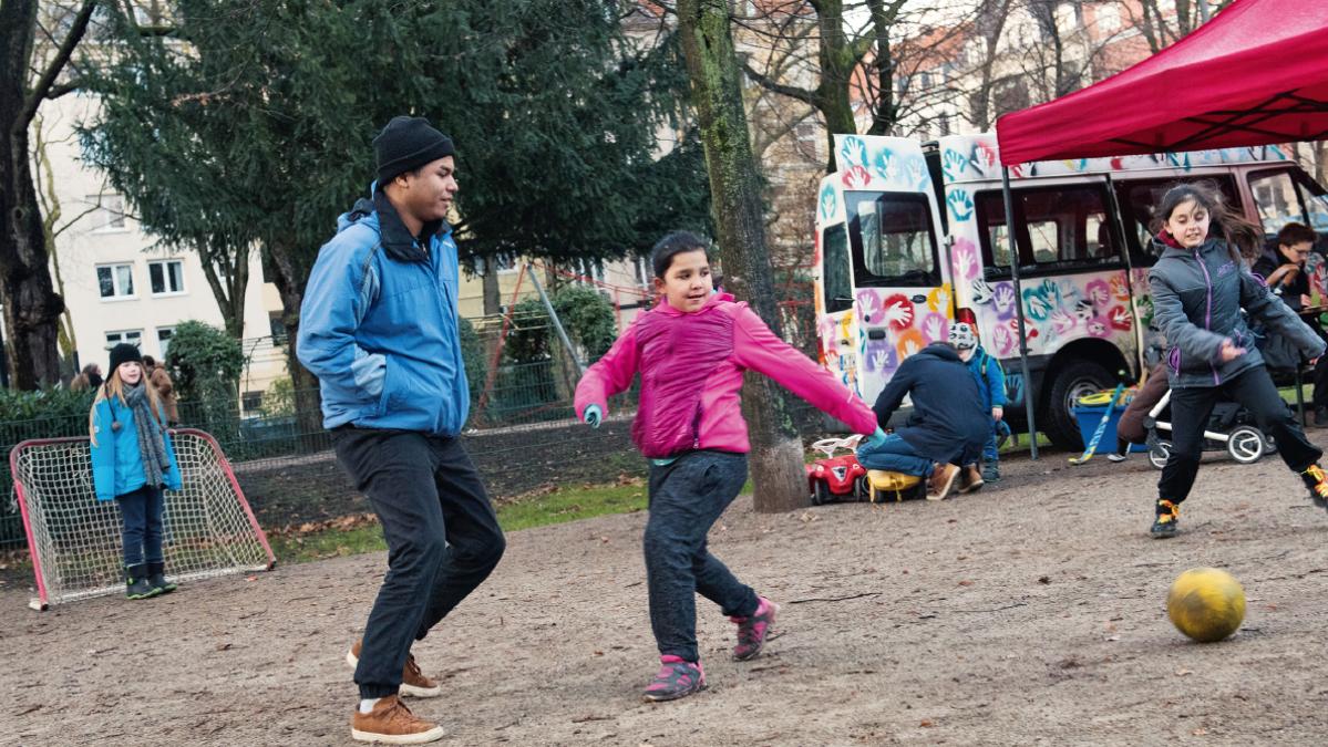 Am Spielmobil der Kölner Caritas treffen sich Kinder aus unterschiedlichen Ländern. Mitten drin Wilver Valencia aus Kolumbien. © Bettina Flitner / MISEREOR