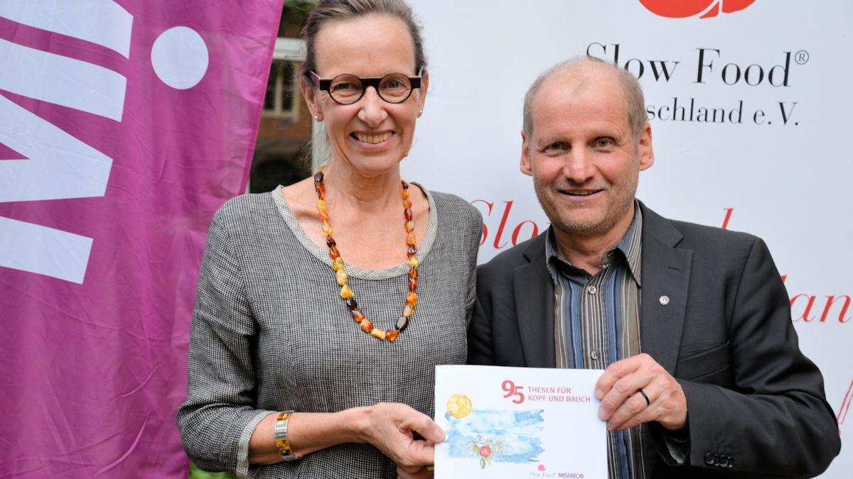 """Dr. Ursula Hudson, Vorstandsvorsitzende von Slow Food Deutschland, und MISEREOR-Hauptgeschäftsführer Pirmin Spiegel halten stolz die gemeinsame Broschüre """"95 Thesen für Kopf und Bauch"""" hoch. Foto: MISEREOR."""
