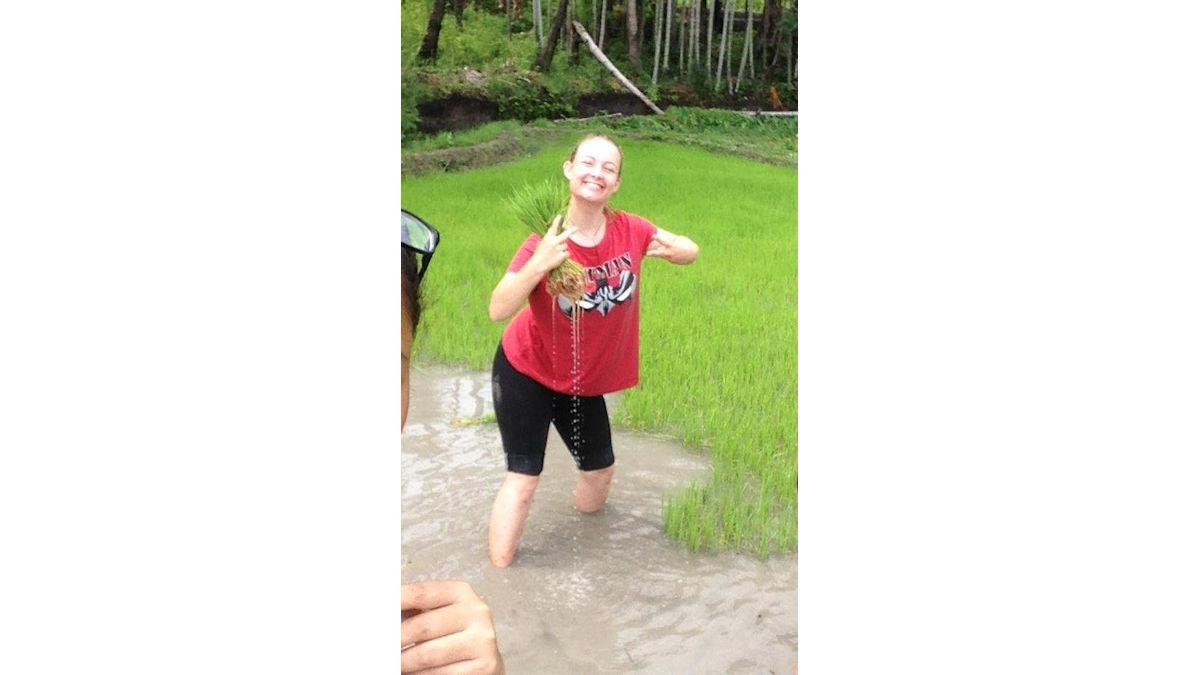 """Leonie, die gerade """"Fukit Hare"""".  Sie zieht die schon etwas gewachsenen Reispflanzen aus dem """"Taho"""" (=Matsch)."""