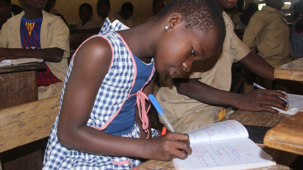 Die Bio-Kakaokooperative ermöglicht den Kindern der Kakaobauern einen unbeschwerten Alltag mit Schulbesuch. Davon profitiert auch Emanuelle. Sie ist ganz vertieft in ihre Aufgabe. © INADES/MISEREOR.