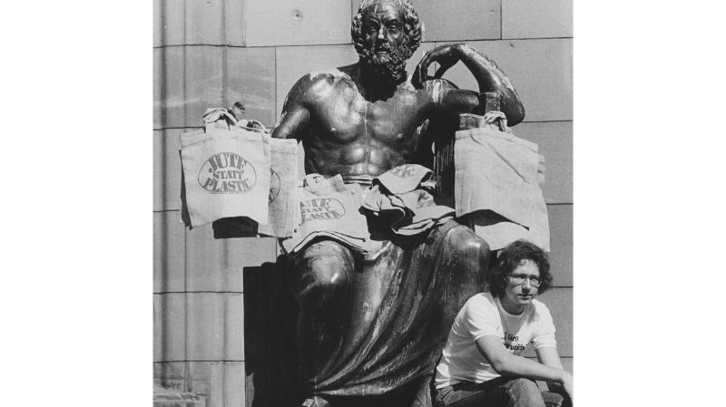 Ein Mann sitzt unterhalb einer Statue, an der Jutetaschen aufgehängt wurden.