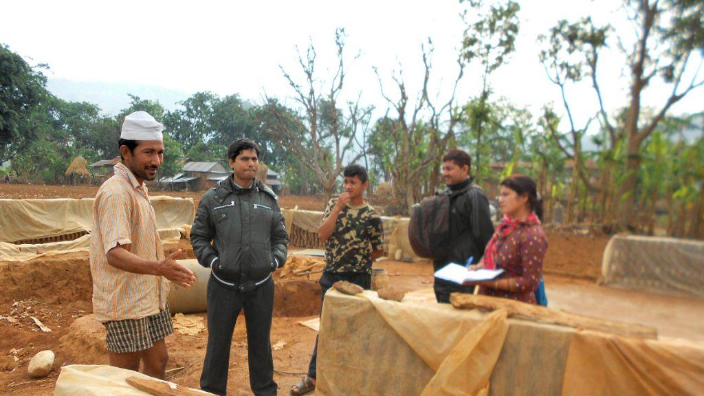 Eine Mitarbeiterin der Integrated Community Development Campaign (ICDC) in Dhading Distrikt spricht mit Arbeitern einer Ziegelproduktion über ihre Situation