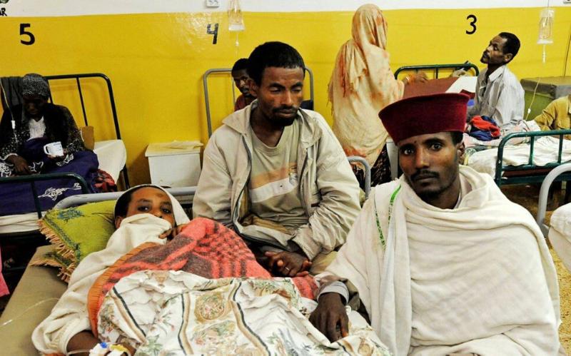 Zwei Männer sitzen neben einem Mann, der im Krankenhaus in einem Bett liegt.