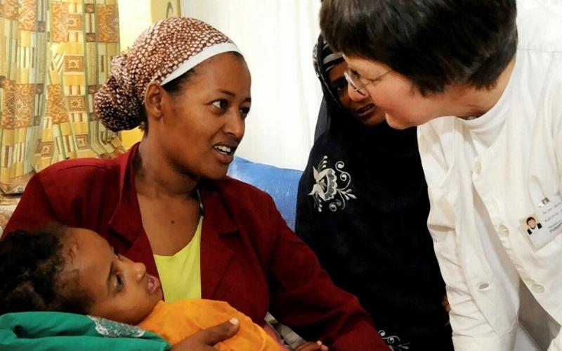 Eine Frau spricht mit einer anderen Frau, die ein Kind in ihrem Arm hält.