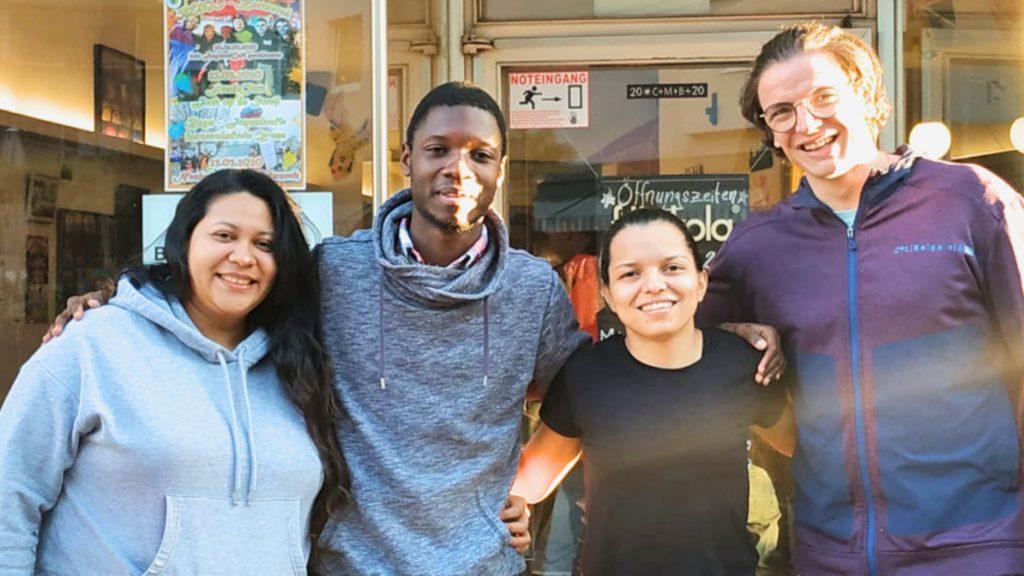 Die Freiwilligen Maria, Lawrent und Mirna miti ihrem Kollegen Lukas vor dem Café Bugs der Caritas in Köln.