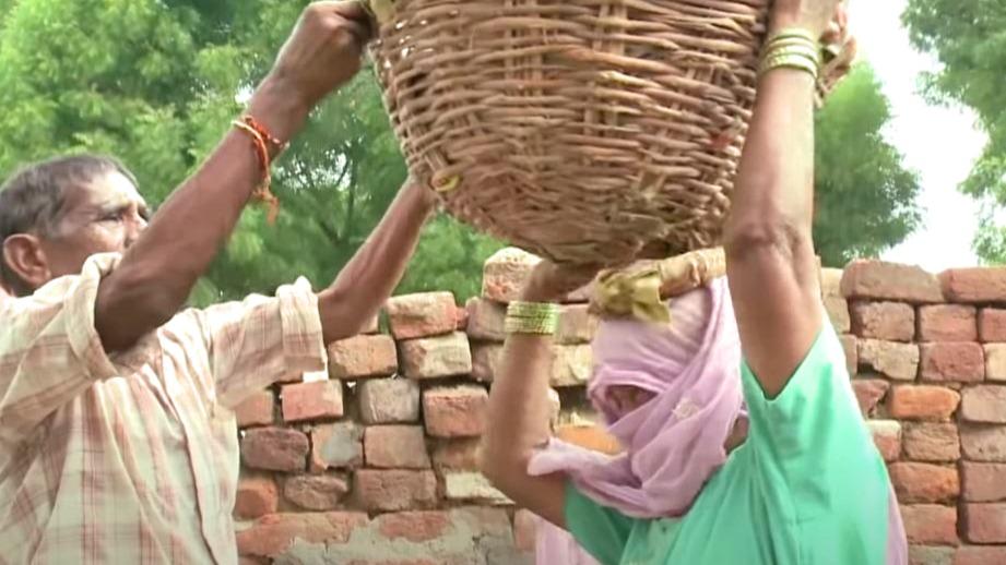 Dalit-Frau in Indien beim Reinigen von Latrinen