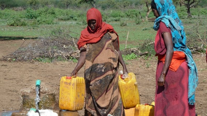 Zwei Frauen tragen Wasserkanister