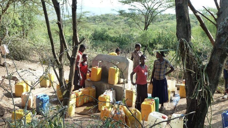 Menschen stehen an einem Brunnen