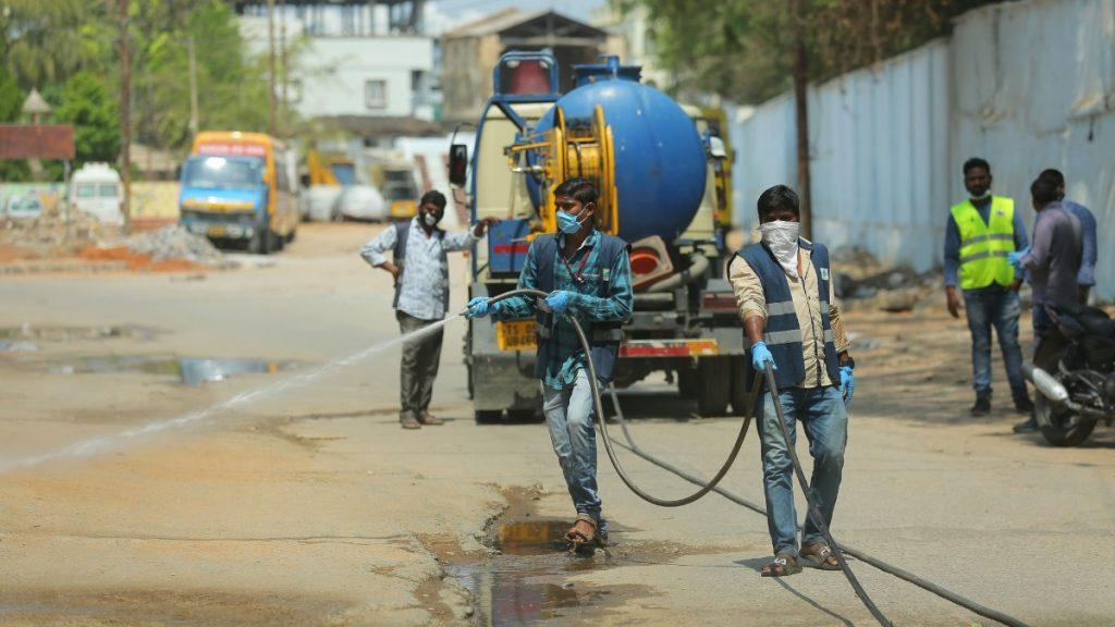 Corona: indische Arbeiter desinfizieren Straßen