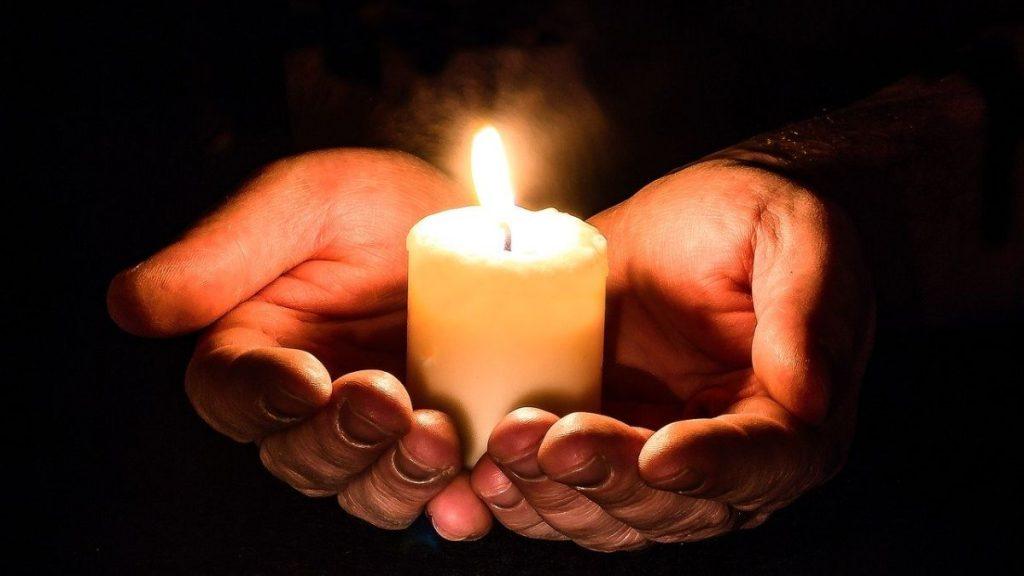 Hände halten Kerze Dunkelheit