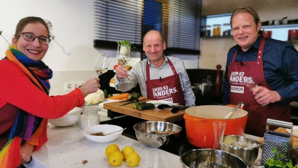 Drei Personen in einer Küche stoßen mit Gläsern zum Fastenessen an